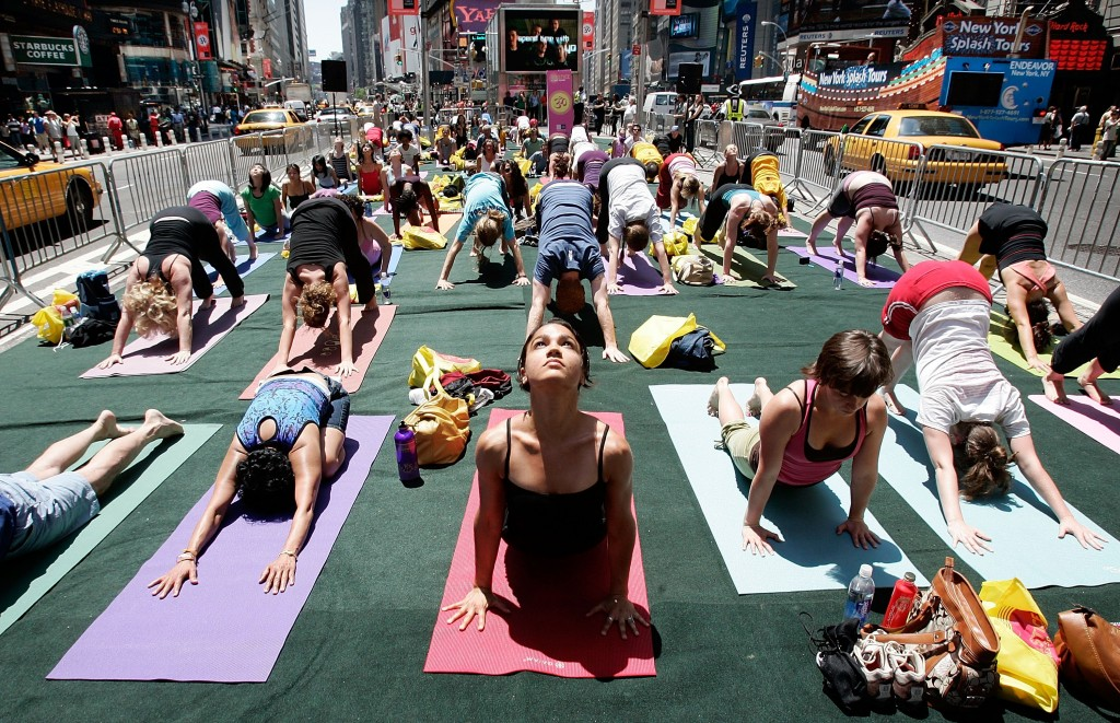 "NEW YORK - JUNE 21: LeTania Kirkland (C) and other yoga enthusiasts from across the country participate in the annual ""Summer Solstice in Times Square Yoga-thon"" June 21, 2007 in New York City. The summer solstice is the first official day of summer and the longest day of the year. (Photo by Mario Tama/Getty Images)"